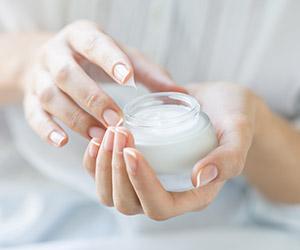 Woman holding jar of cosmetic cream