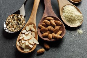 Diced almonds, sliced almonds, whole almonds, almond protein powder in spoons